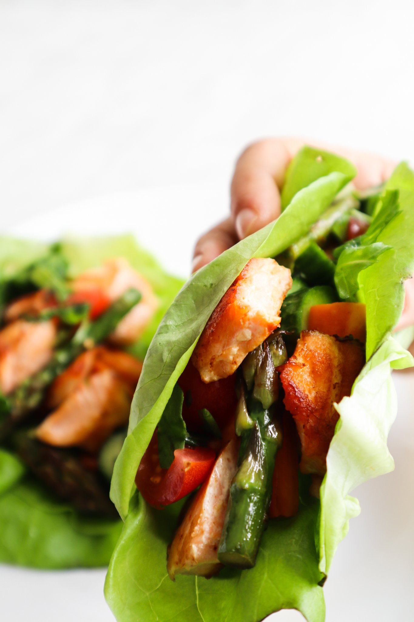Healthy salmon lettuce wraps! This clean eating recipe is the perfect flavorful and delicious low carb dinner idea. Filled with salmon, pan-seared and fresh vegetables and a herby sunflower seed sauce, this is a great anti-inflammatory recipe that you'll want to do again and again if you're following an anti-inflammatory diet