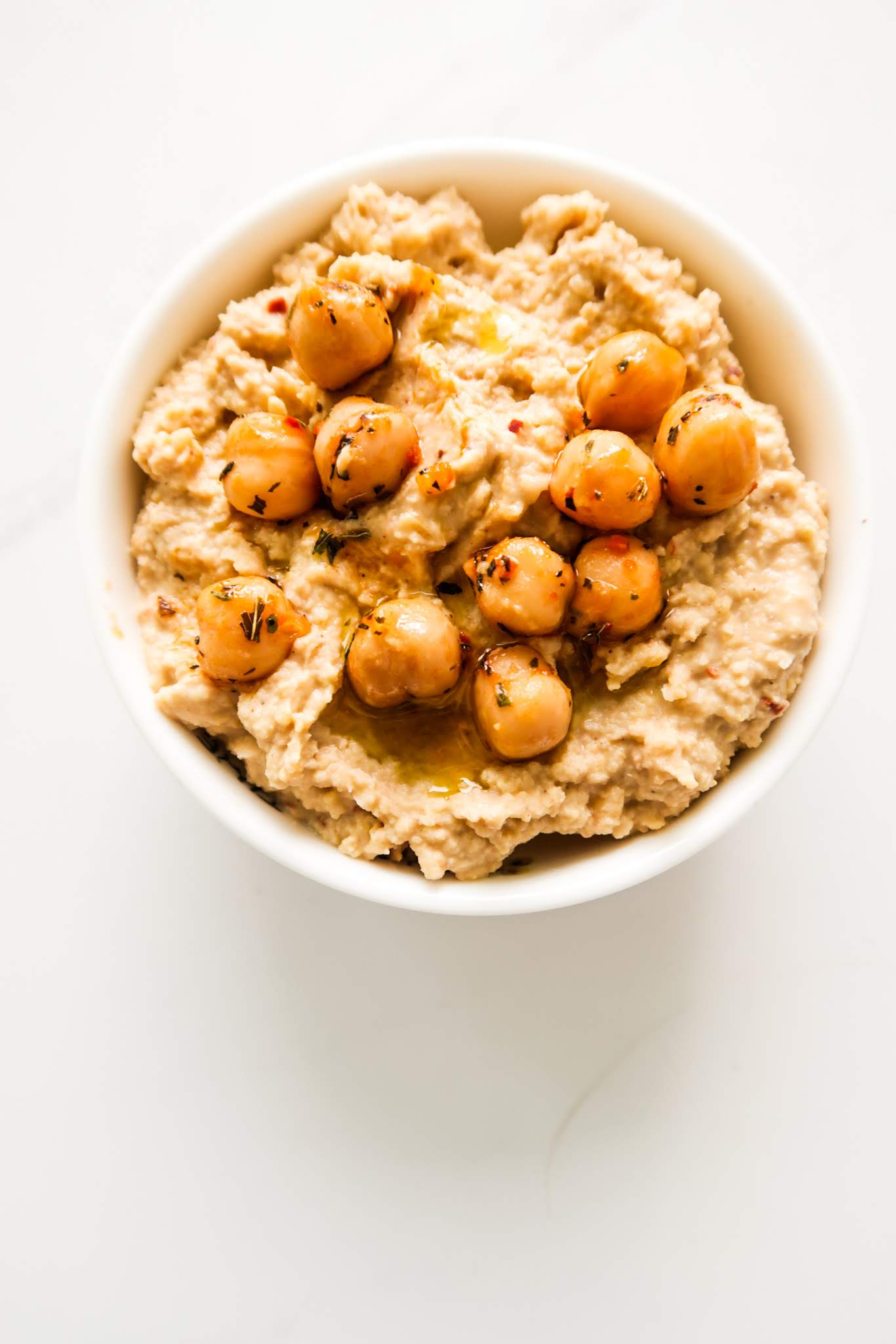 The best hummus! This healthy hummus recipe is spicy, full of flavor and just the best snack, ingredient in dinner or lunch bowls or healthy wraps! Your dinner table needs this easy hummus recipe. It's only 5 ingredients - chickpeas, tahini, garlic, crushed red pepper and lemon juice and it's ready in 5 minutes.