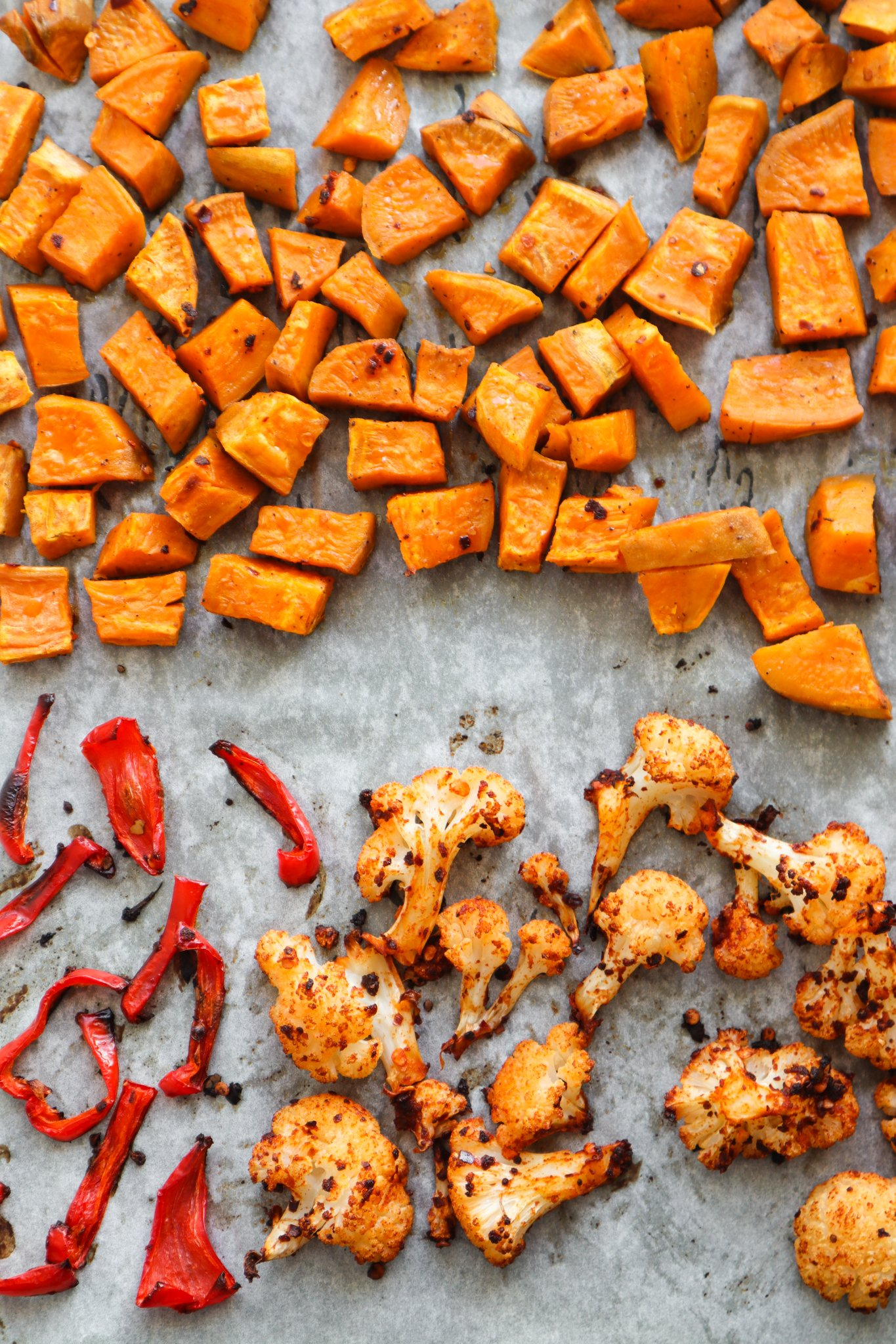 A super easy roasted vegetable recipe for spicy roasted cauliflower, sweet potatoes and a sad little red pepper. This healthy side dish recipe is great for meal prep, vegan, gluten free and paleo.