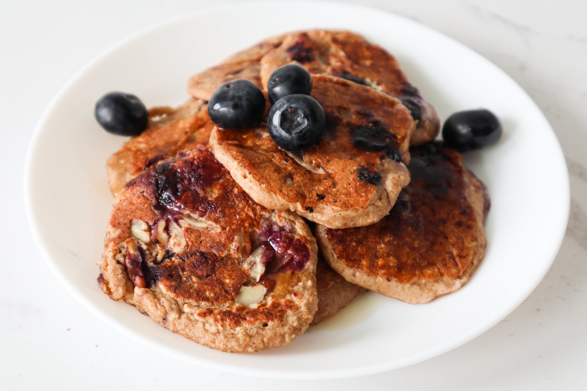 These vegan blueberry banana oatmeal pancakes are the easiest, best healthy gluten free dairy free breakfast idea! Made with oats, fruit, seeds and nuts this vegan oatmeal pancake recipe is nutritious and super tasty!