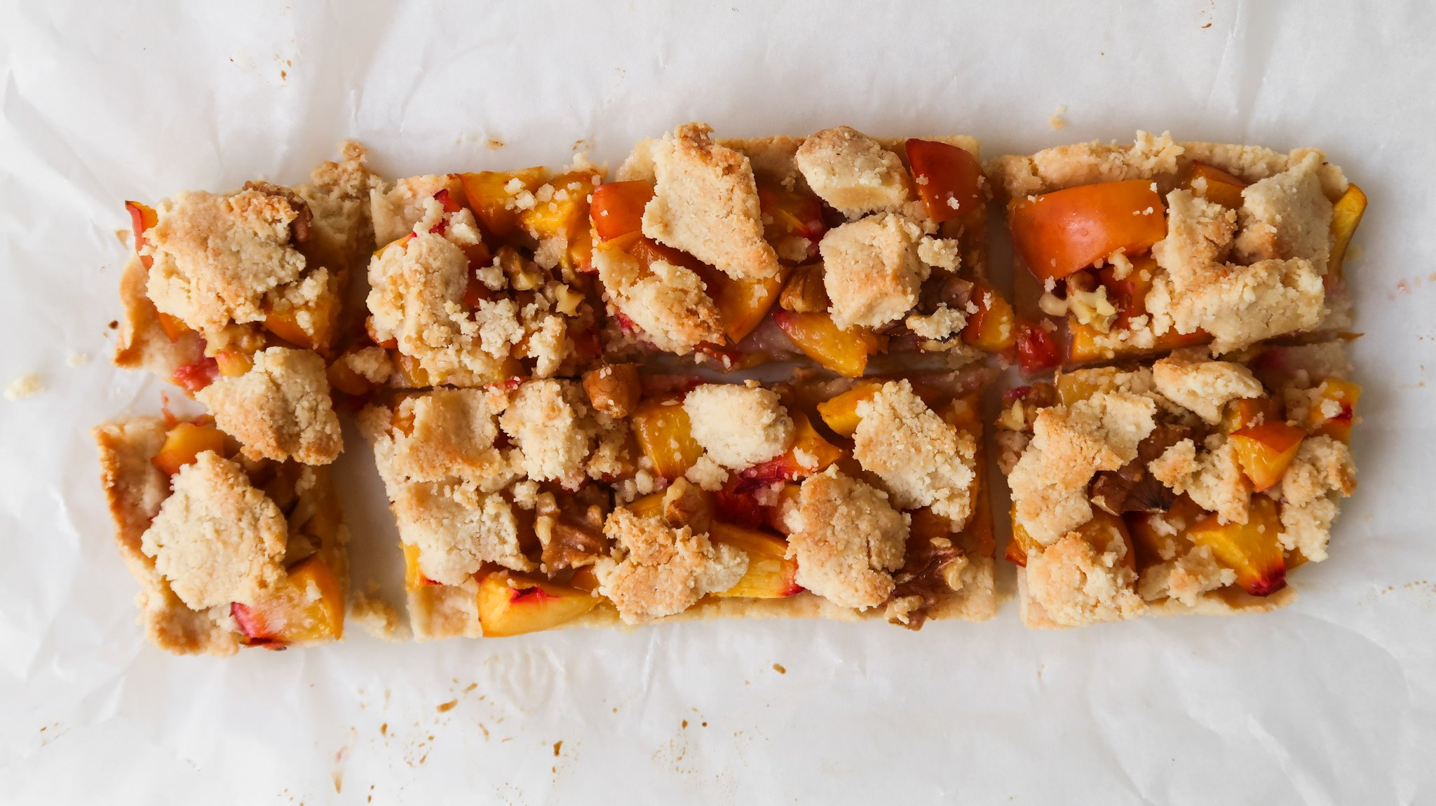 This healthy peach crumble bars recipe is made with simple ingredients, no refined sugar, is gluten-free, dairy-free, paleo and vegan. This is such an easy peach dessert recipe that gets better in the fridge! Easy and healthy peach recipe for snack or breakfast that you can make in 20 minutes.